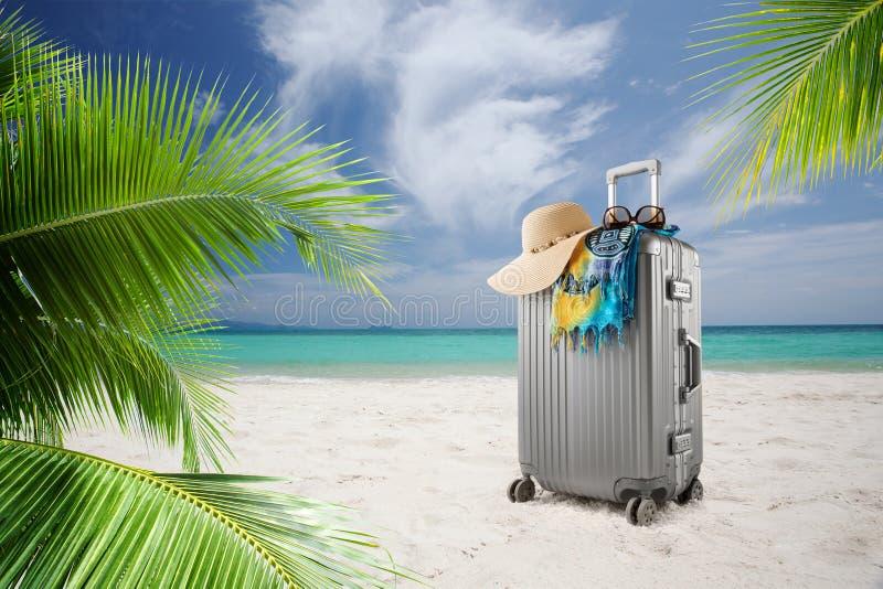 valise avec le chapeau, le pareo et les lunettes de soleil sur la plage tropicale ensoleill?e images stock