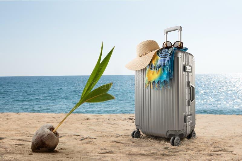 valise avec le chapeau, le pareo et les lunettes de soleil sur la plage tropicale ensoleill?e photographie stock