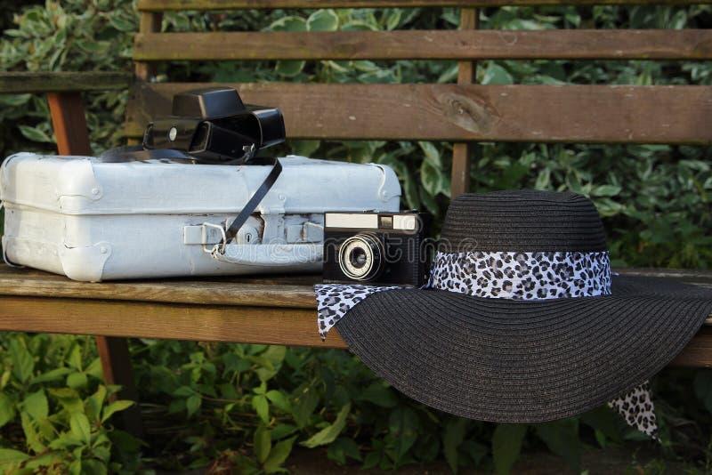 Download Valise Blanche, Le Vieil Appareil-photo Et Chapeau Sur Un Banc Dans Un Jardin Photo stock - Image du appareil, valise: 76080514