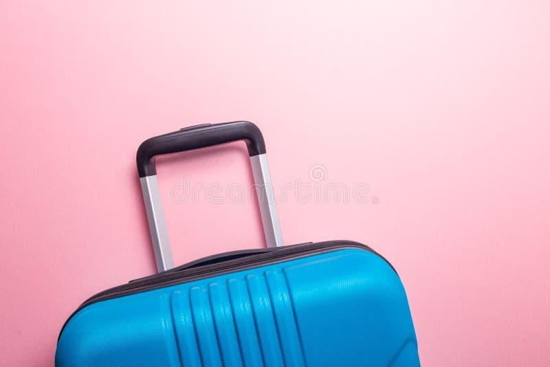 Valise bleue des vacances d'été créatives roses en pastel de fond, vacances, concept de voyage images libres de droits