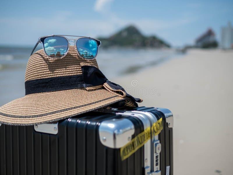 Valise, chapeaux et lunettes de soleil de voyage sur un océan de plage à l'arrière-plan Mer tropicale, conception de l'avant-proj image libre de droits