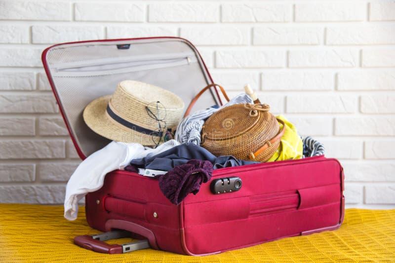 Valise complètement de l'habillement des femmes pendant des vacances d'été images libres de droits