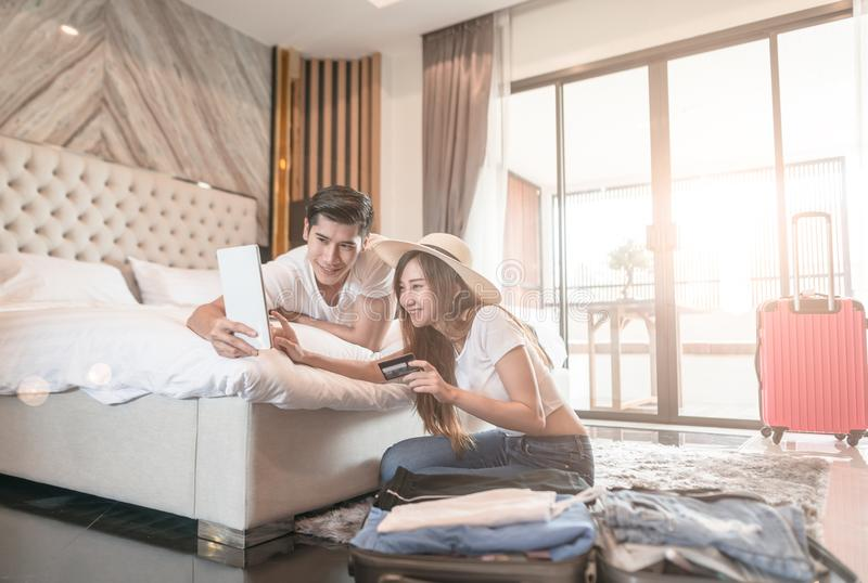 Valise d'emballage de couples sur le plancher dans le comprimé d'utilisation de pièce pour le salaire en ligne de voyage de voyag photo stock
