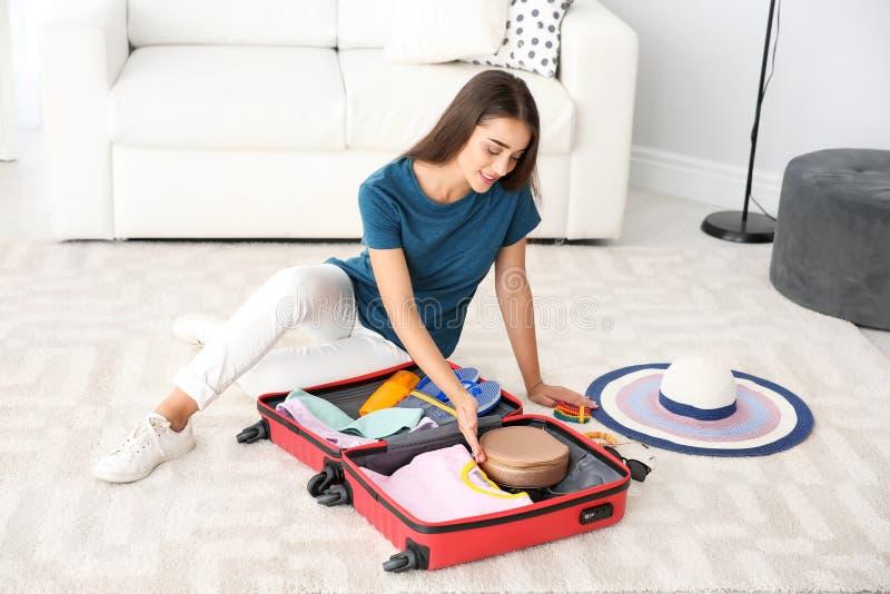 Valise d'emballage de jeune femme à la maison images libres de droits