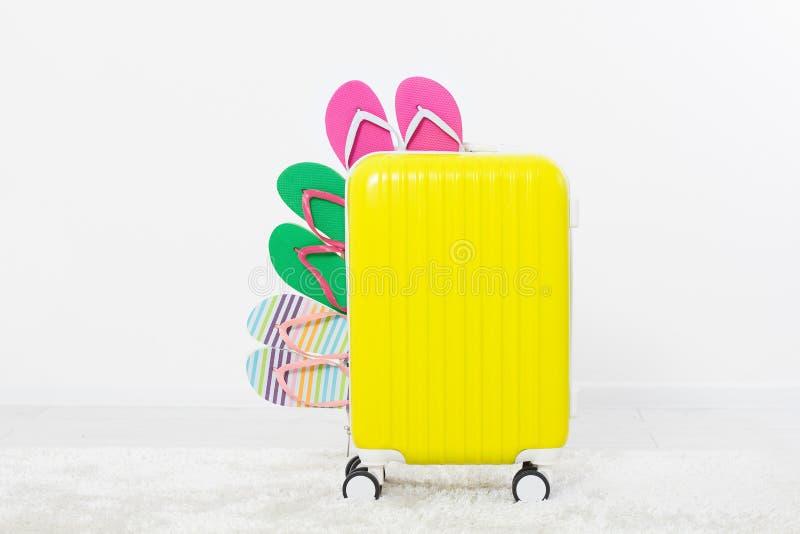 Valise d'isolement les vacances d'été blanches de fond bascules électroniques ou pantoufles d'été Plage de sandales Chapeau rouge image stock