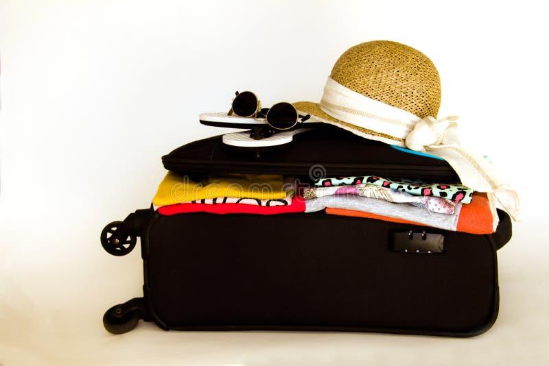 Valise de vacances avec des vêtements, lunettes de soleil de chapeau image stock