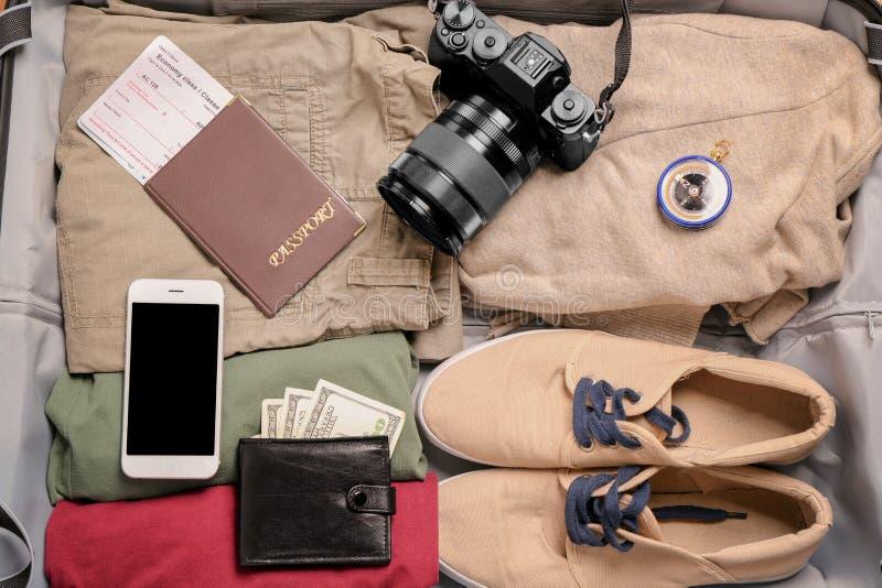 Valise emballée avec la caméra, le passeport, le téléphone portable et l'argent concept de course images libres de droits