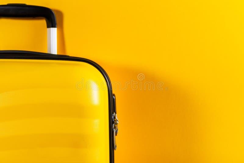 Valise lumineuse et élégante de taille de cabine sur le fond jaune lumineux photographie stock