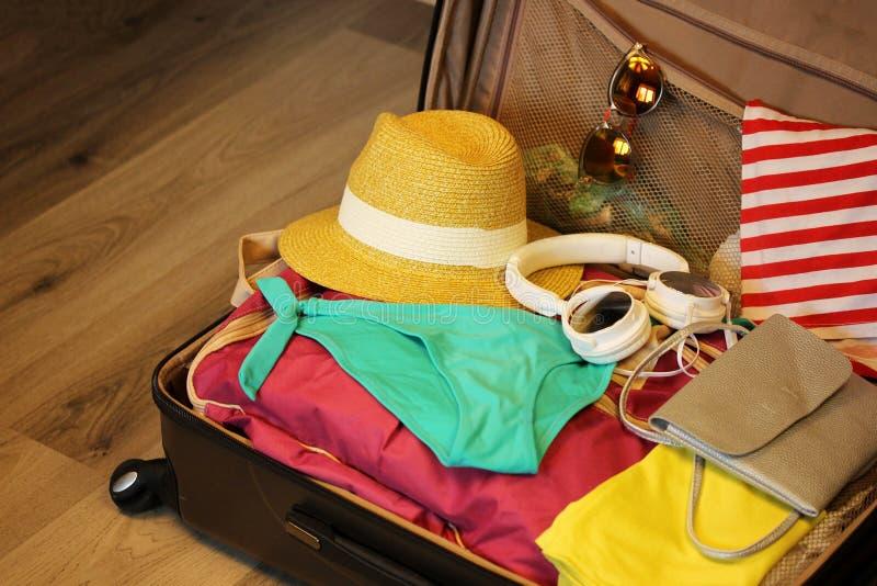 Valise rassemblée pour le voyage Valise en plan rapproché ouvert de vue avec des choses au repos sur un fond en bois photographie stock