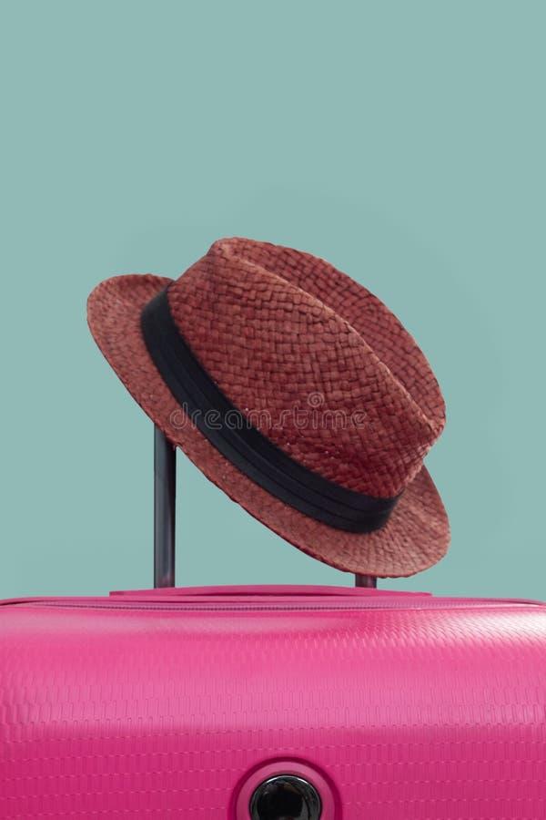 Valise rose avec le chapeau sur le fond rose en pastel concept de course images stock