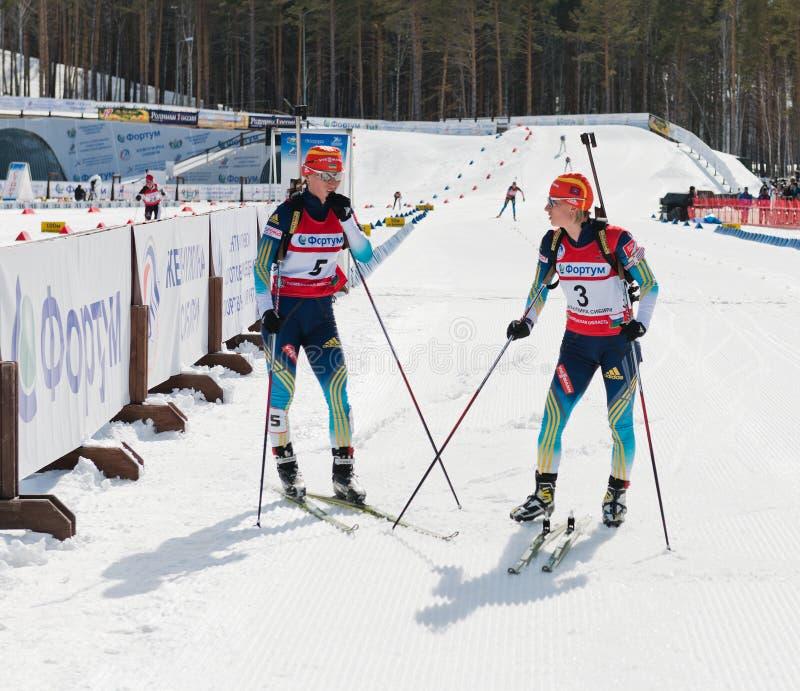 Valj och Vita Semerenko (UKR) efter fullföljande på Biathlonkvinnor 13 arkivfoto