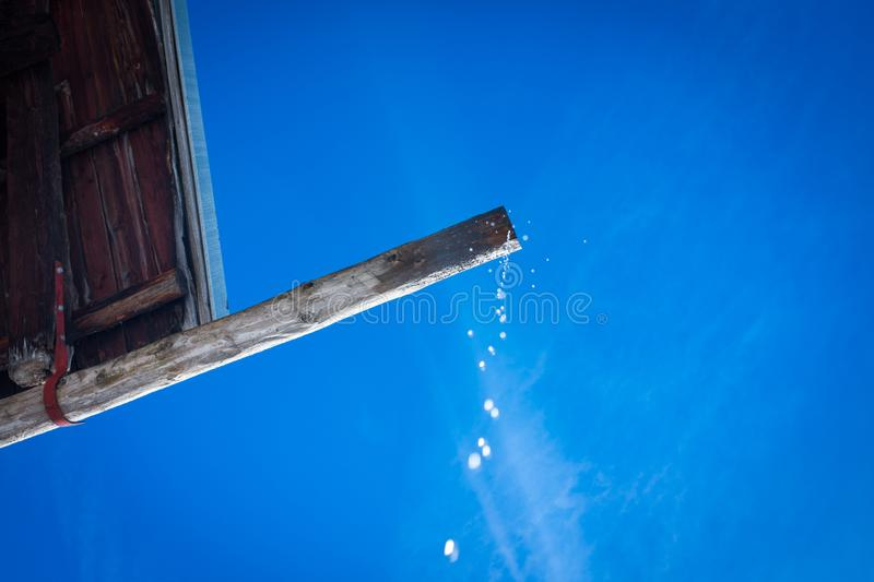 Drop falling from an old wooden roof stock photography