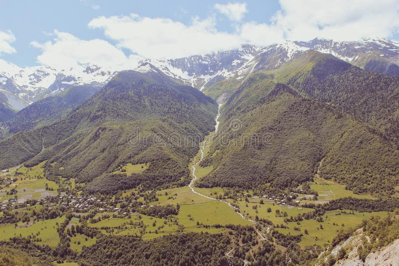 Vall?e sc?nique dans les montagnes de Caucase avec un petit village, des verts d'?t? et des cr?tes couronn?es de neige image libre de droits
