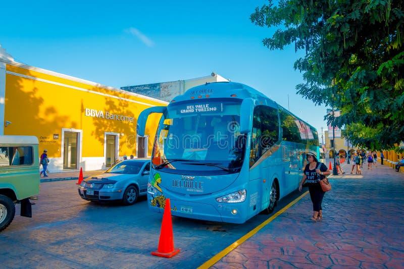 VALLADOLID, MÉXICO - 12 DE NOVEMBRO DE 2017: Mulher não identificada que anda perto de um parket do ônibus do touristict na rua d foto de stock royalty free