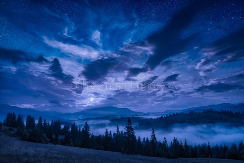 Valle de la montaña con las estrellas en un cielo nocturno nublado imagenes de archivo