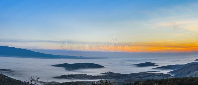 Valle de la montaña de la niebla y de la nube en la puesta del sol fotografía de archivo
