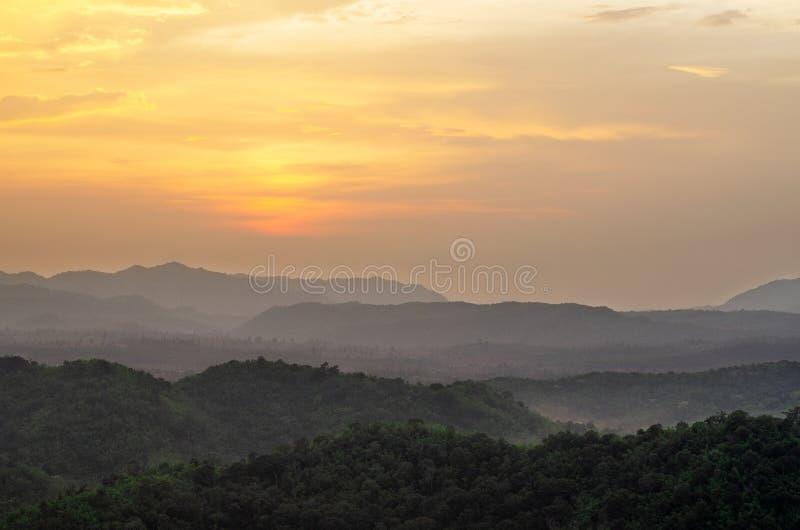 Valle de la montaña en la niebla durante puesta del sol fotos de archivo libres de regalías