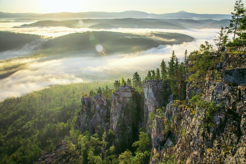 Valle della montagna durante l'alba dorata Annebbi e si rannuvola la foresta evidenziata dal sole di mattina immagine stock