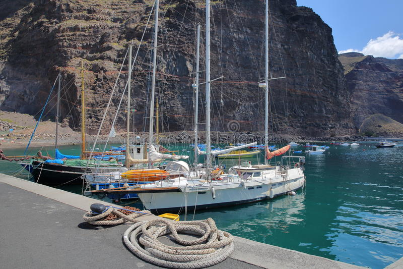VALLE GRAN REY, LA GOMERA, SPAIN - MARCH 19, 2017: The village of Vueltas with sailing boats and cliffs in the background. The village of Vueltas with sailing royalty free stock photography