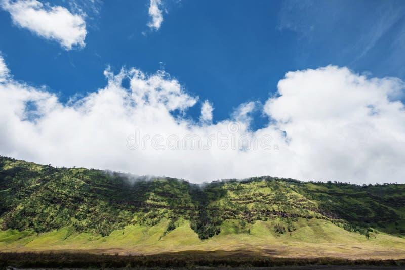 Valle verde con paisaje de la pradera con el cielo azul y las nubes imagenes de archivo