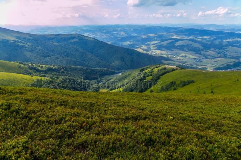 Valle verde de la montaña con pequeñas depresiones contra la perspectiva del cielo azul sin fin imagenes de archivo