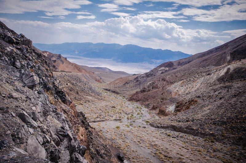 Valle y un lavado del desierto llenado de las rocas, de la arena y de la artemisa en el parque nacional de Death Valley en Califo foto de archivo