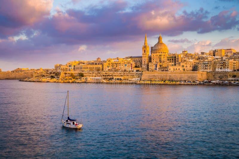 Valletta, de Kathedraal van Malta - van StPaul ` s in gouden uur bij de hoofdstad Valletta van Malta ` s met zeilboot en mooie kl stock afbeelding