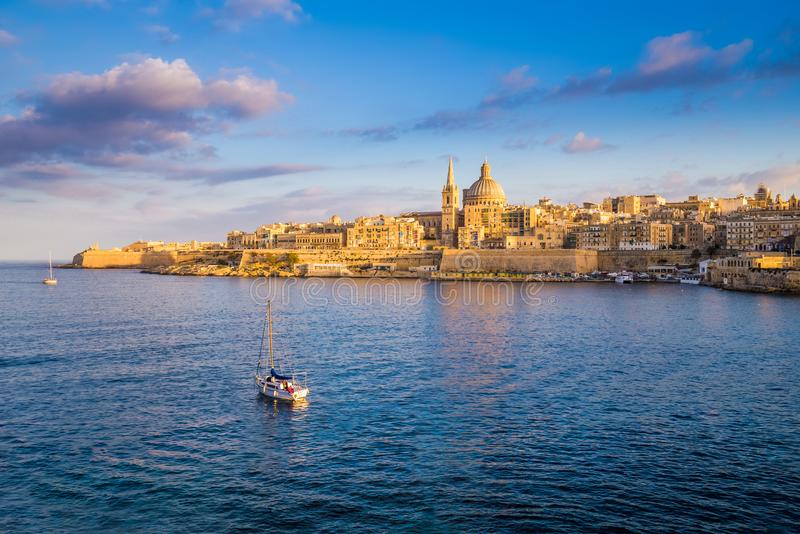Valletta, Malta - żagiel łódź przy ścianami Valletta z StPaul ` s katedrą fotografia stock