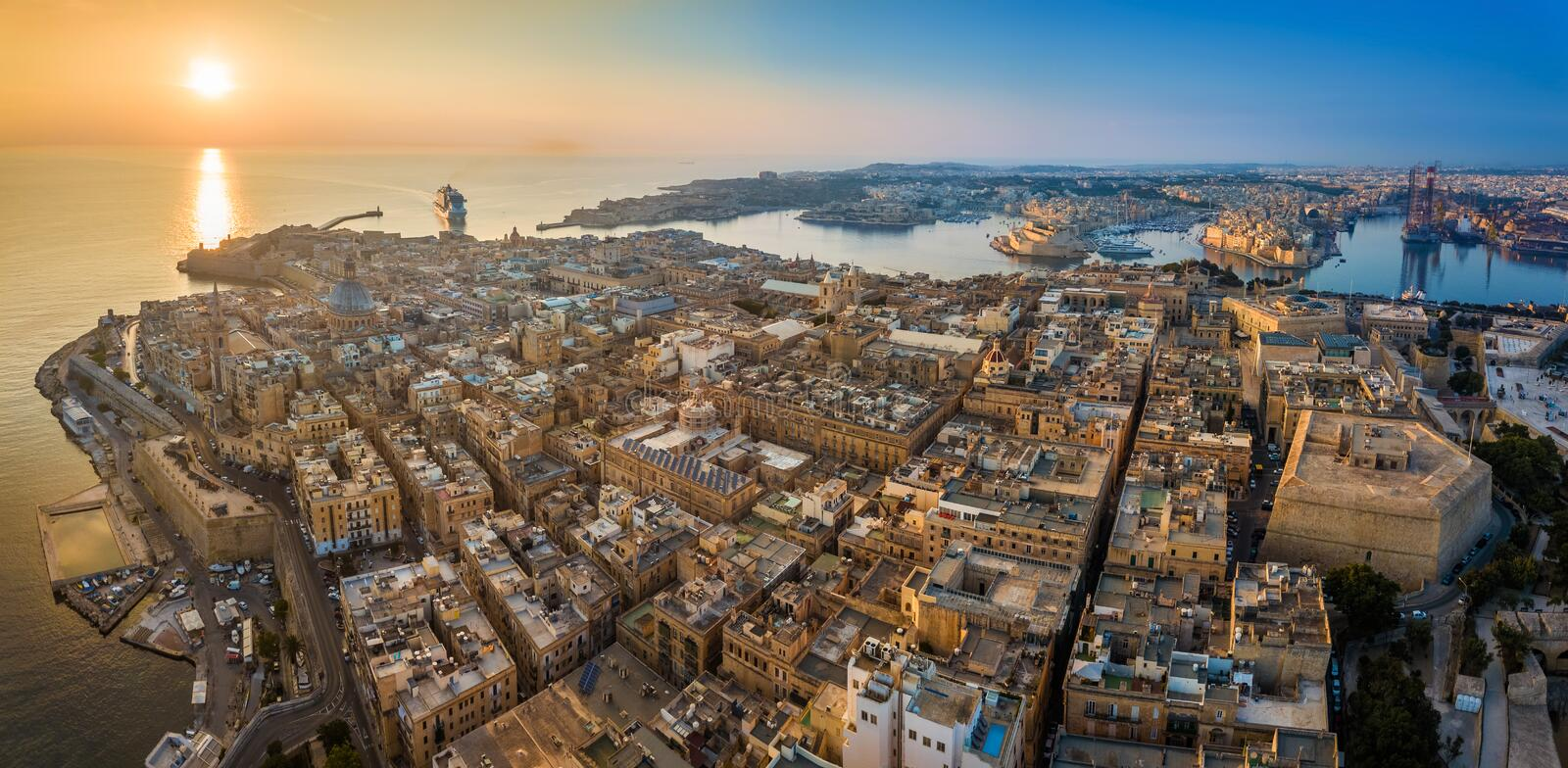 Valletta, Malta - Aerial panoramic skyline view of Valletta at sunrise with cruise ship entering at Grand Harbor royalty free stock photos