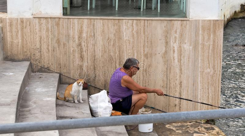 Fisher and Cat. Red and white cat waiting for fisherman to catch fish. Valletta, Malta - August 30, 2019: Fisher and Cat. Red and white cat waiting for fisherman royalty free stock photography