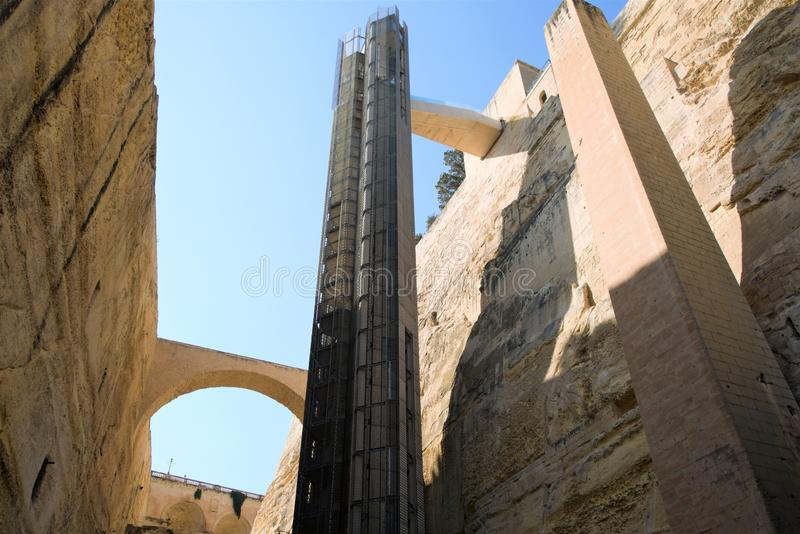 Valletta, Malta, August 2019. Modern high-speed elevator among the walls of the old fortress. A beautiful courtyard amidst huge walls of yellow Maltese stone royalty free stock images