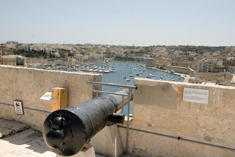 Valletta, Malta, August 2019. Old cannon and view from the fort wall. A magnificent view from the high fortress wall over the blue waters of the bay with royalty free stock photos