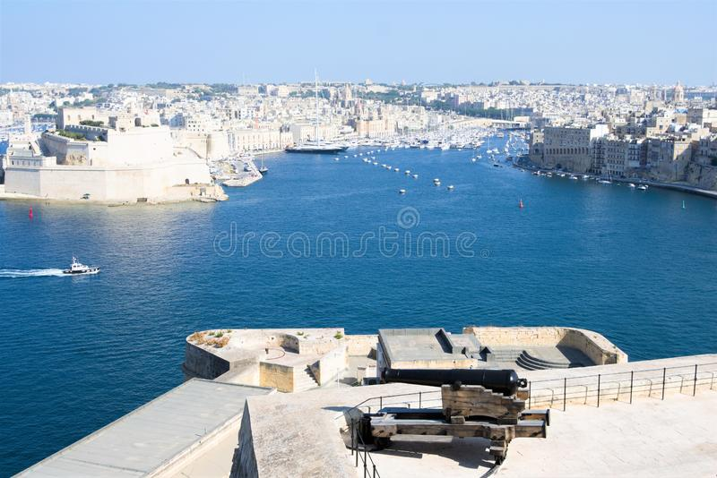 Valletta, Malta, August 2019. An old cannon on the wall of the fortress and a view of the Great Harbor. royalty free stock image