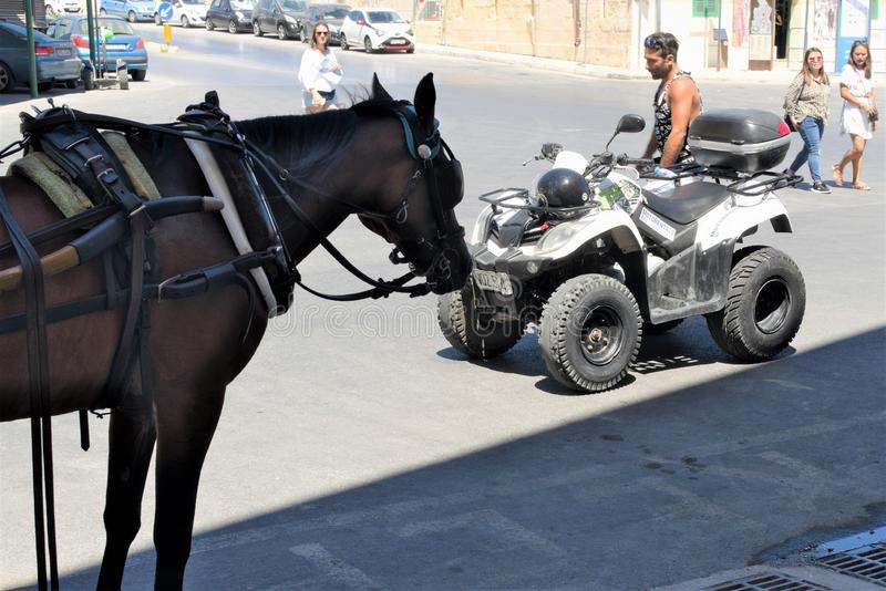 Valletta, Malta, August 2019. People of the island. A motorcyclist and a horse look at each other in surprise. Diverse people on the island, tourists and locals royalty free stock images