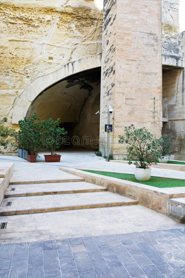 Valletta, Malta, August 2019. View of the courtyard of the fortress with an elevator to the wall. A beautiful courtyard amidst huge walls of yellow Maltese stock photos