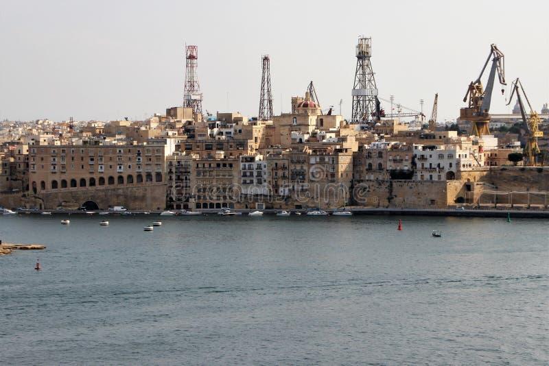 Valletta Malta, Augusti 2015 Sort av den forntida staden och de moderna portkranarna royaltyfri bild