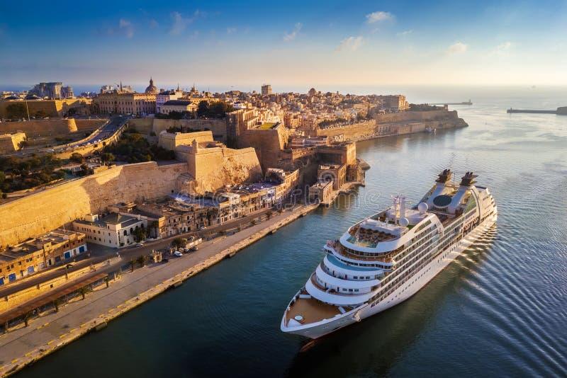 Valletta, Malta - kruis schip die in Grote Haven bij zonsopgang met de oude stad van Valletta varen stock afbeeldingen