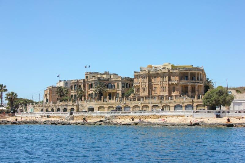 Valletta Malta - Maj 2018: Gamla byggnader i storslagen hamn Turister som kopplar av på den steniga stranden arkivbilder