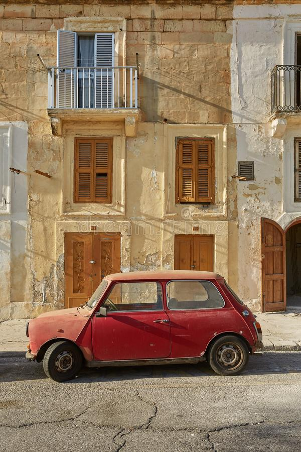 Old vintage car in front of typical traditional house in Valletta in Malta royalty free stock image