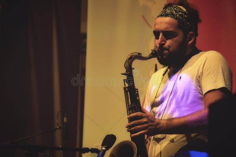 Valletta / Malta - September 1 2019: A young man with a beard playing the saxophone on stage at a music festival royalty free stock images
