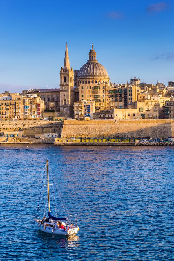 Valletta, Malta - St. Paul`s Cathedral in golden hour at Malta`s capital city Valletta with sailboat. And beautiful blue sky royalty free stock photos