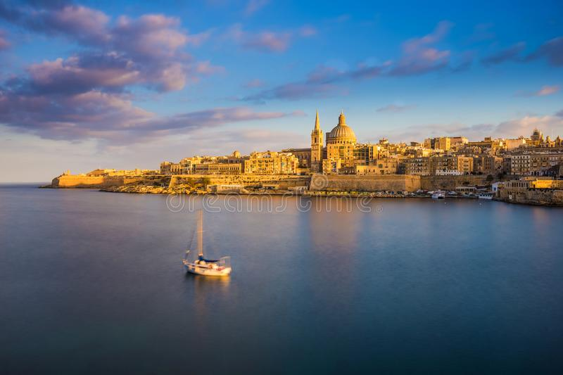 Valletta, Malta - St.Paul`s Cathedral in golden hour at Malta`s capital city Valletta with sailboat. And beautiful colorful sky and clouds stock photography