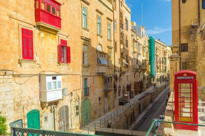 Valletta-streetview mit roten Balkonen und Telefonzelle - Malta lizenzfreie stockfotos
