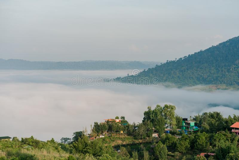 A valley Below the thick white fog Covered throughout the area There are a number of houses on the cliff side.  stock image