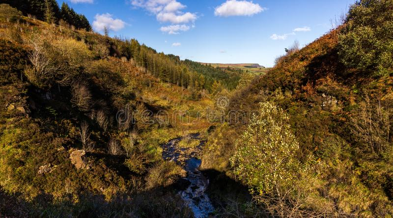 Valley with bushes and trees in beautiful autumn colors with river beneath and puffy clouds in blue sky royalty free stock photos