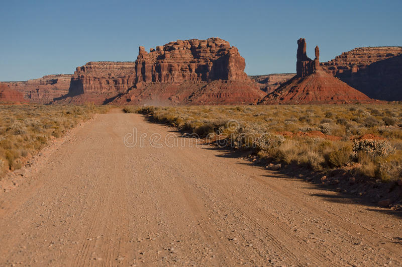 Valley of Gods mesas. Dirt road trough the scenic Valley of God, with sandstone mesas formation in the background and desert vegetation on the side stock photo