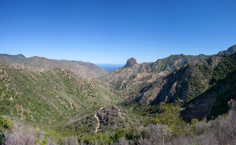 The valley of Vallehermoso northbound. The elongated valley of Vallehermoso in La Gomera, Canary Islands, Spain, northbound. In the middle the distinctive rock royalty free stock photo