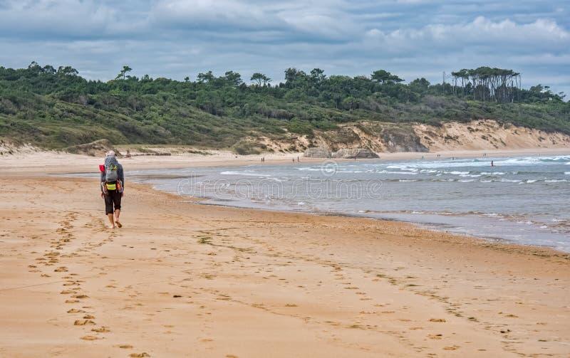 Vallfärda med ryggsäcken som går på stranden på Camino de Santiago royaltyfria bilder
