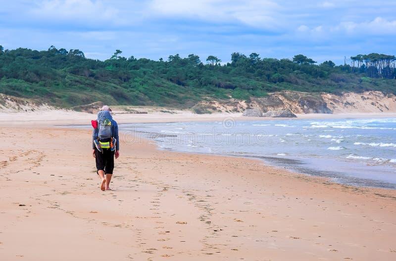 Vallfärda med ryggsäcken som går på stranden på den norr vägen Camino de royaltyfri foto