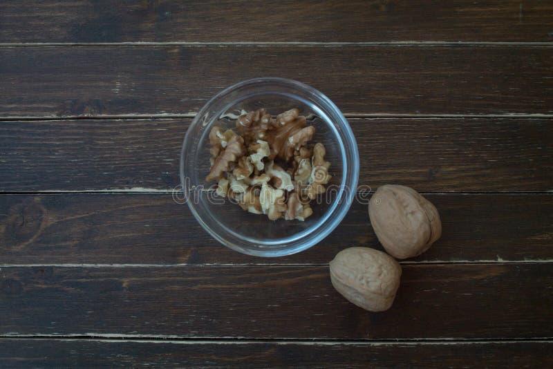 Valnötter i en genomskinlig bunke på trä från över arkivfoto